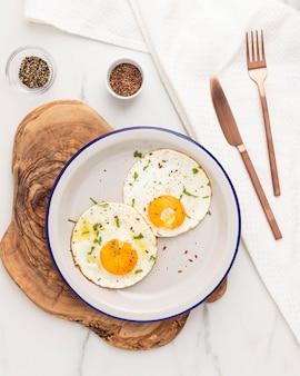Плоская кладка яичницы на завтрак на тарелке со столовыми приборами