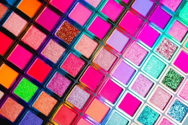 Плоская планировка сломанных ярких разноцветных теней для век как образцы и образцы косметического продукта, изолированные на белом фоне.
