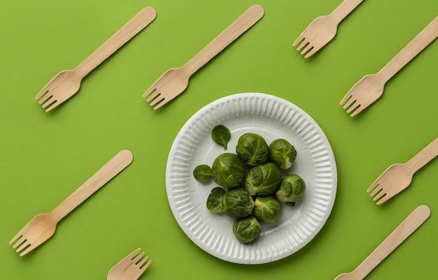 Плоская планировка брюссельской капусты на тарелке с деревянными вилками