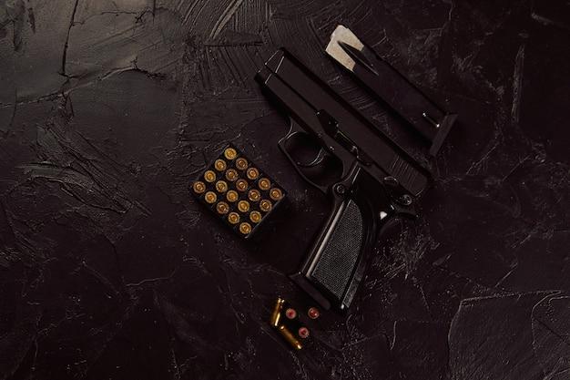 コンクリートの背景にカートリッジと銃を平らに置き、黒いテーブルの武器にピストルと弾丸を置きます。