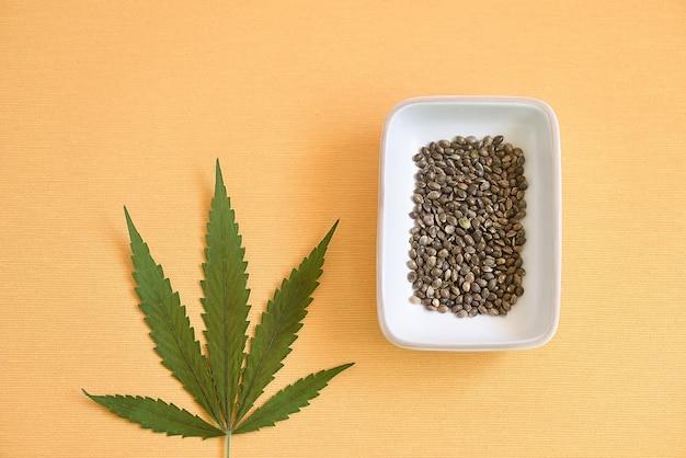 Плоское расположение семян cbd в миске и лист марихуаны на оранжевом фоне ткани.