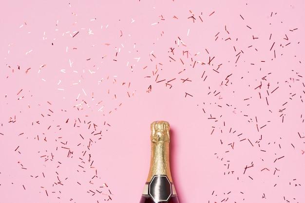 お祝いのフラットレイ。ピンクの背景にカラフルなパーティーストリーマーとシャンパンボトル。