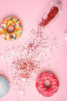 축하의 평평한 위치. 분홍색 배경에 화려한 파티 깃발과 맛있는 도넛이 있는 샴페인 유리.