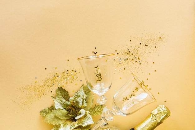 お祝いのフラットレイ。黄色の背景にシャンパンとギフト用のグラス2杯