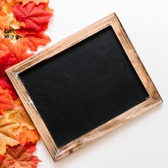 Flat lay of chalkboard and autumn leaves