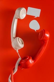 두 개의 전화 수신기와 코드가있는 채팅 거품의 평면 배치