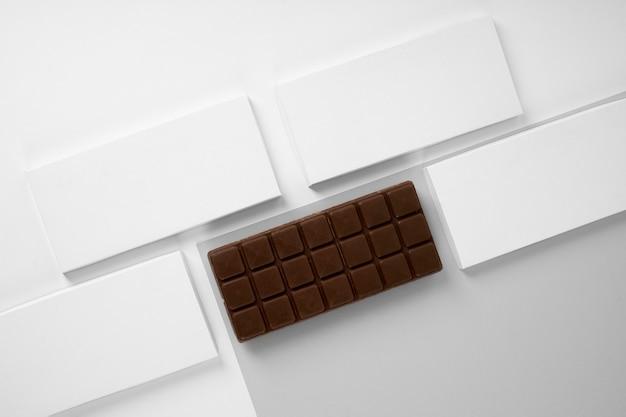 Плоская планировка плитки шоколада с упаковкой и копией пространства