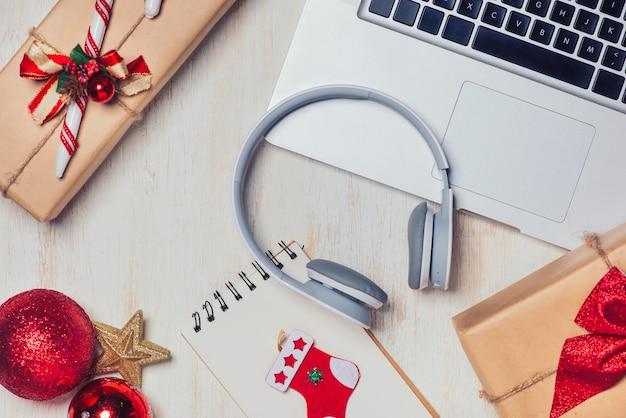 白い木製の背景の上のラップトップとクリスマスプレゼントのフラットレイ