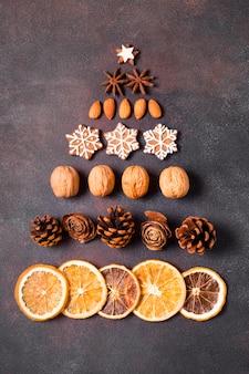 ジンジャーブレッドと乾燥した柑橘類で作られたクリスマスツリーの形のフラットレイ