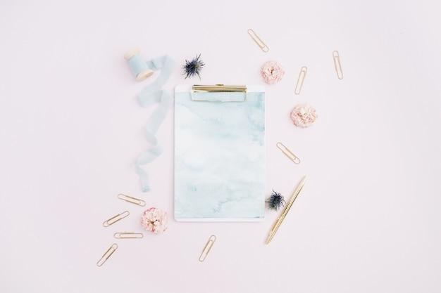 クリップボード、バラのつぼみ、青いリボン、金色のペン、淡いピンクのクリップのフラットレイ
