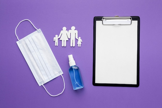 Плоский буфер обмена с медицинской маской и семьей из бумаги