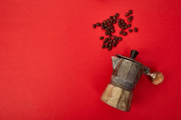 Плоская планировка кофеварки и кофейных зерен на красном фоне.