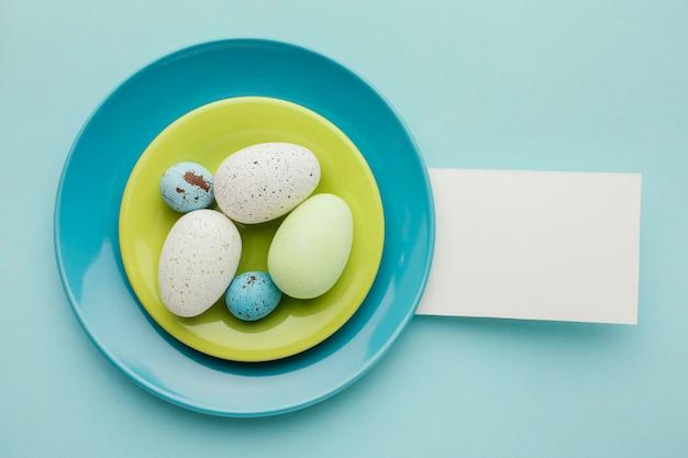Плоская кладка цветных пасхальных яиц на тарелках с бумагой