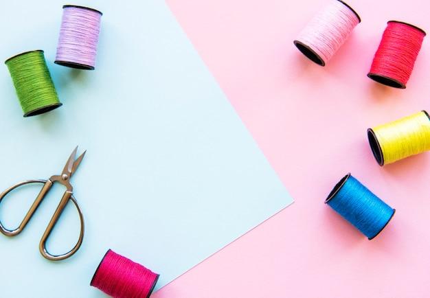 2トーンの背景、縫製と裁縫の概念で縫うための色付きの糸ロールとはさみのフラットレイ。