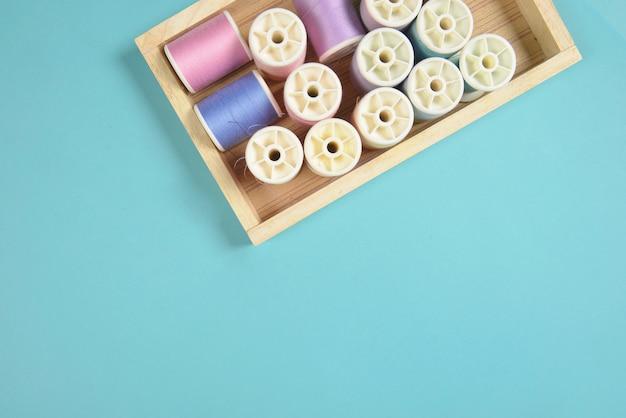 파란색 배경에 바느질 컬러 스레드 롤의 평평하다