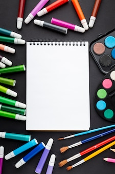 Плоская раскладка красочных маркеров с блокнотом