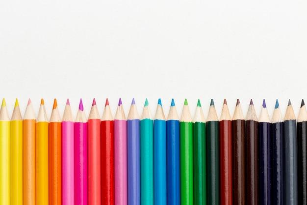 Плоская планировка красочных карандашей с копией пространства
