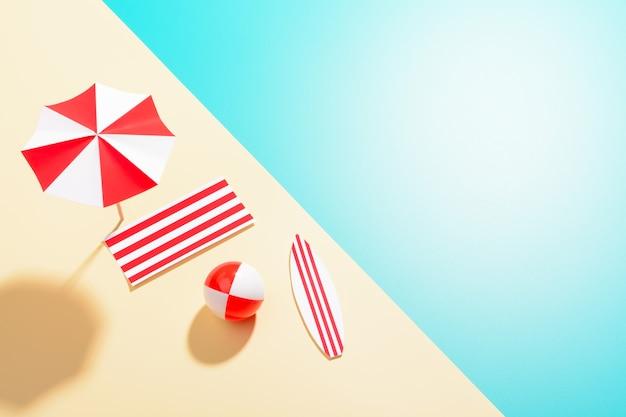 해변에 화려한 우산이 평평하게 놓여 있고 여러 가지 빛깔의 표면에 재미있는 물건이 있습니다.
