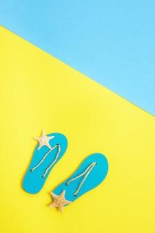 여름 신발-슬리퍼와 밝은 종이에 작은 불가사리가있는 해변 라운지 공간의 구성된 미니어처 플랫 누워.