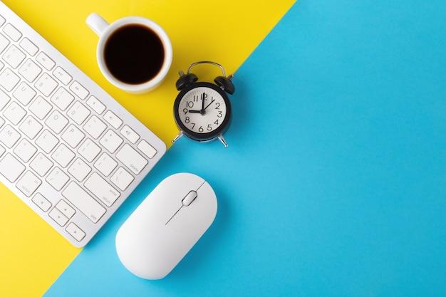 時計とコーヒーカップとコンピューターのキーボードとマウスのフラットレイ