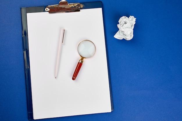Плоский план концепции поисковой идеи, целей, делового имиджа, увеличительного стекла и скомканной бумаги на синем фоне, поиска лучшей идеи и вдохновения среди прочего, поискового маркетинга.