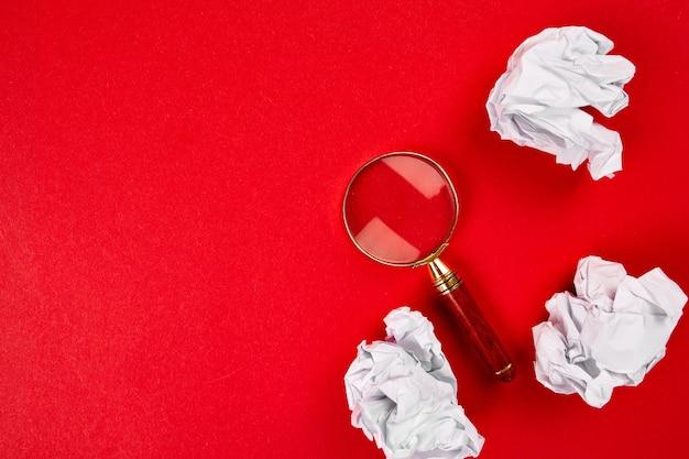 Плоский план концепции поисковой идеи, целей, делового имиджа, увеличительного стекла и скомканной бумаги на красном фоне, поиск лучшей идеи и вдохновения среди прочего, маркетинг в поисковых системах.