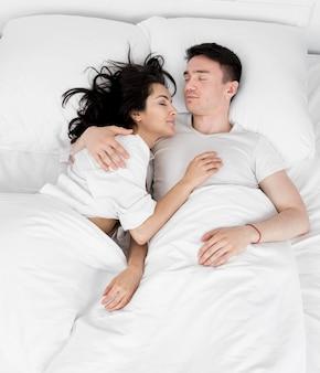Плоская планировка пары, спящей вместе в постели