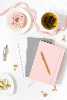 ドーナツとノートブックと緑茶のカップのフラットレイ