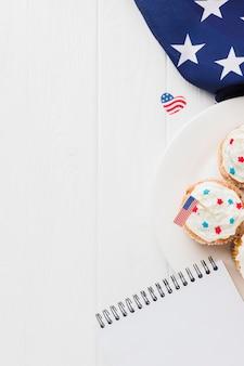 Плоские лежал кексы с американским флагом и блокнотом
