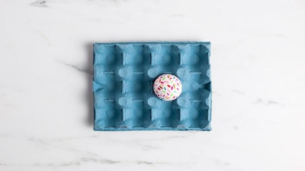 Плоская кладка украшенного пасхального яйца в картонной коробке