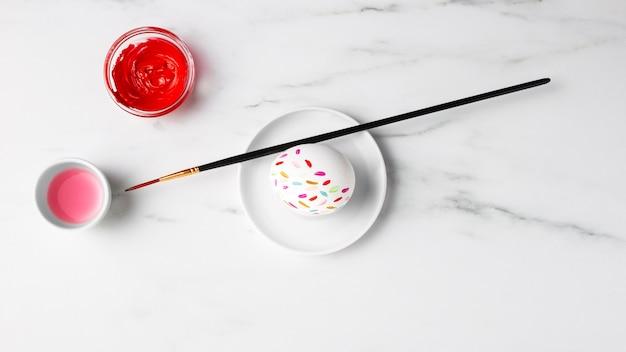 Плоская кладка украшенного пасхального яйца на тарелке с краской и кистью
