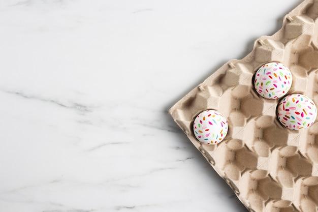 Плоская кладка украшенных пасхальных яиц в картонной коробке с копией пространства