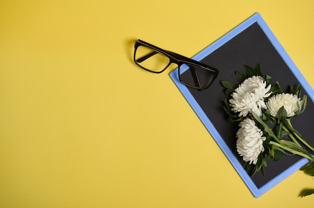 Плоская планировка нежного красивого букета осенних цветов астры и очков на пустой пустой доске с пространством для текста, изолированного на желтом фоне