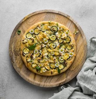 カモミールの花が付いたおいしい調理済みピザのフラットレイ