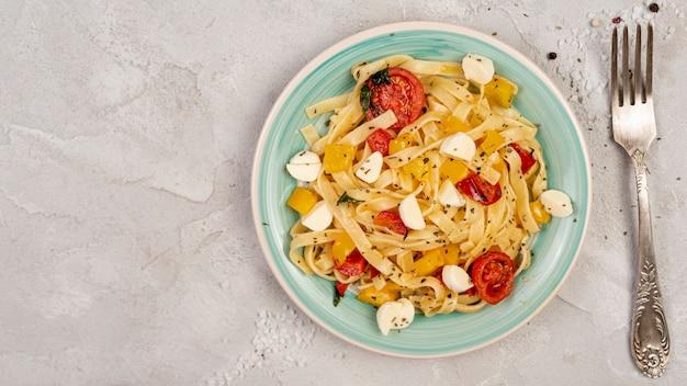 Плоская планировка вкусной итальянской пасты на простом фоне