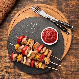 Плоская выкладка вкусного шашлыка на грифельной доске с кетчупом и столовыми приборами
