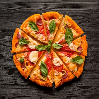 木製のテーブルにおいしいピザのコンセプトのフラットレイアウト