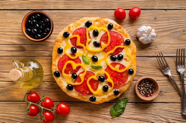 木製のテーブルにおいしいピザのフラットレイアウト