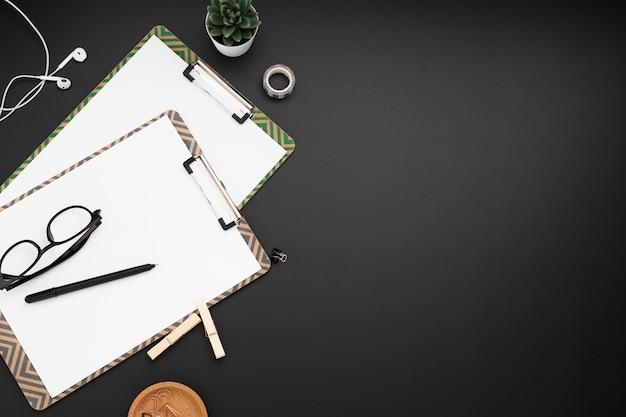 Плоский рабочий стол с блокнотами и наушниками