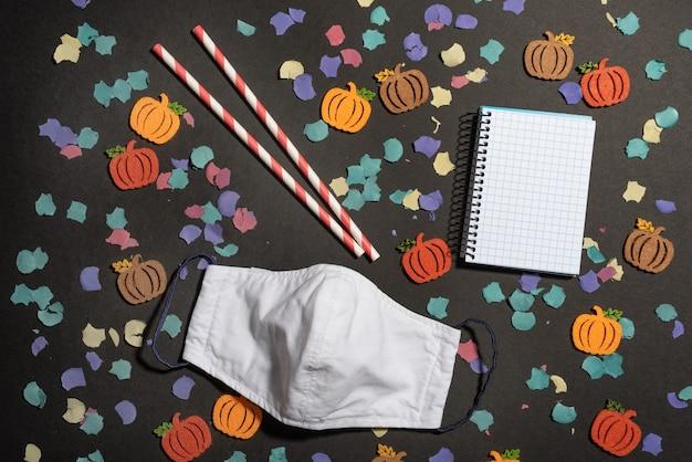 顔のマスクとノートブックと黒い机の上に秋の色のdiyカボチャのフラットレイ