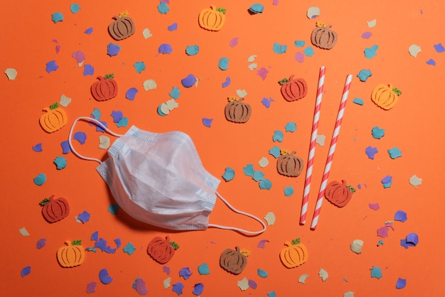オレンジ色の机と顔のマスクに秋の色のdiyカボチャのフラットレイ