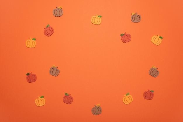 オレンジ色の机の上に秋の色のdiyカボチャのフラットレイ