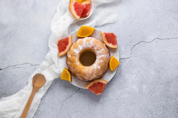 Плоская кладка пончика на тарелку с цитрусовыми
