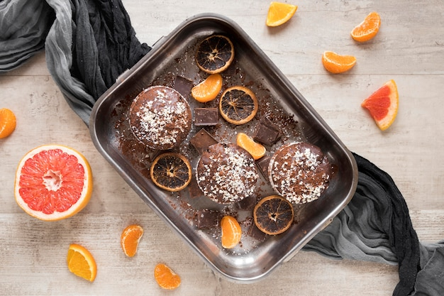 Плоская кладка пончиков в металлическом подносе с цитрусовыми и тканью