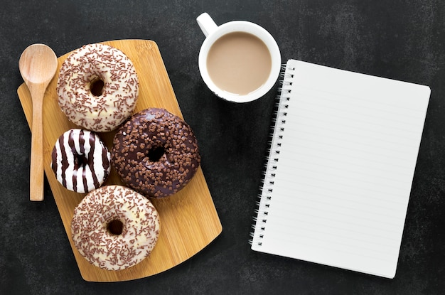 Плоские лежат пончики на разделочную доску с ноутбуком и кофе