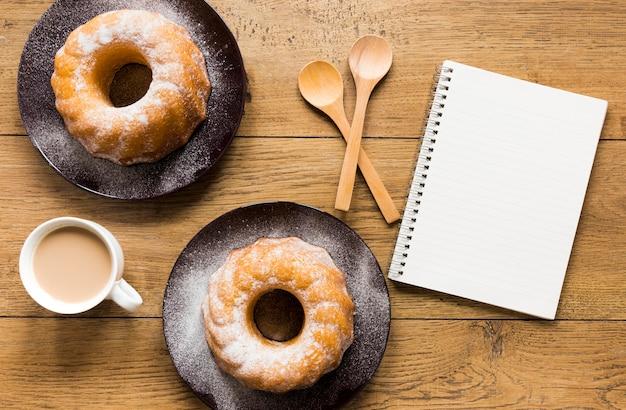 ノートと木製のスプーンで皿にドーナツのフラットレイアウト