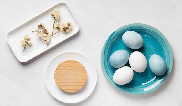 Плоская кладка пасхальных яиц и цветов на тарелках