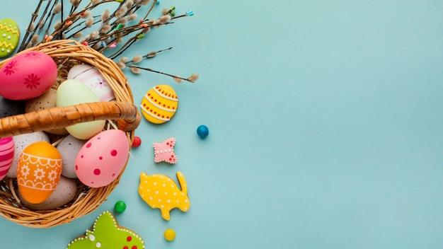 Плоская кладка пасхальных яиц в корзине с фигурами кролика и бабочки