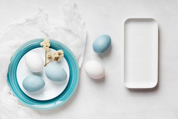 Плоская кладка пасхальных яиц на тарелках с цветами