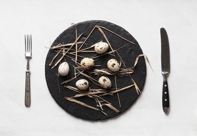 Плоская кладка пасхальных яиц на сланце со столовыми приборами
